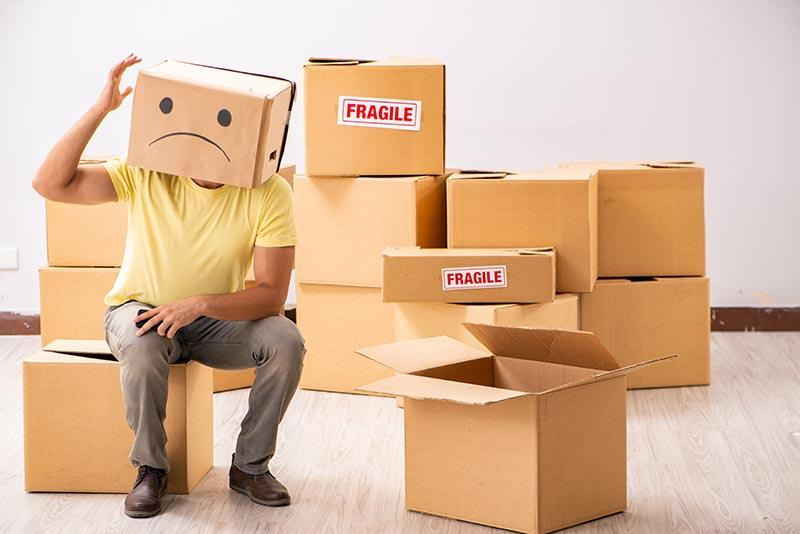 Unhappy man stressed about moving all these boxes to his new home