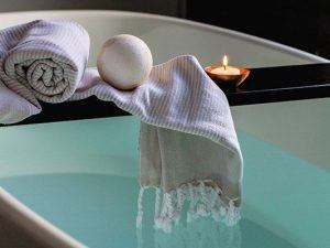 A semi-unrolled towel, bath bomb, and lit candle is perched on a piece of wood that stretches over a calm filled spa.