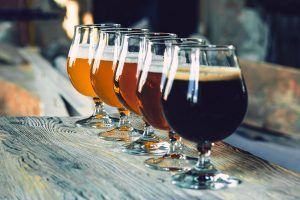 5 glasses of different styles of craft beer ranging from lightest in the back to darkest on the front on wooden table,