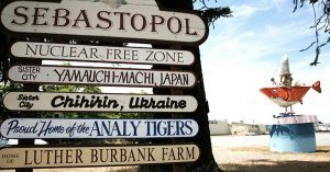 The Welcome to Sebastopol sign with fun facts about the town such as its sister cities and local high school sports team. In the background is sculpture art of an orange shark and clown fisherman that is popular in the area.