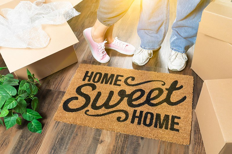 A couple placing their doormat after a successful move