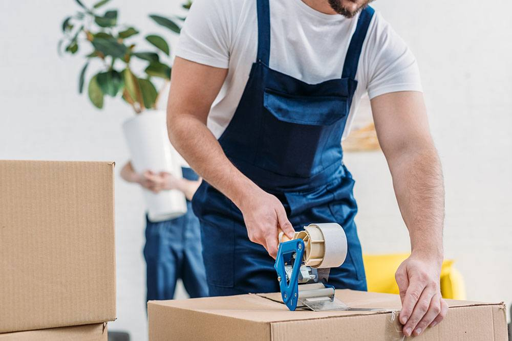 professional full services mover packing a moving box during a home move